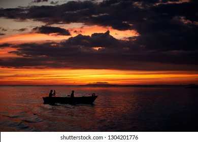 Two fishermen return home at sunset. Art view on tropic nature.Tarcoles river, Costa Rica.