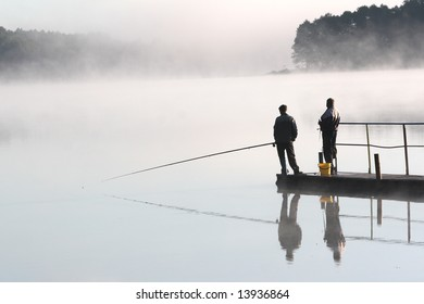 Two fishermen waiting for a fish on misty morning