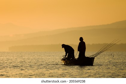 Two fishermen's silhouette standing on boat in dawn