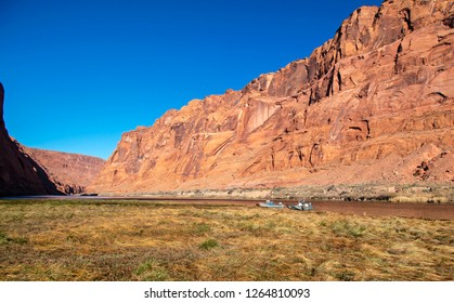 Two fishing boats anchored on shore of Colorado river near Glen Canyon dam with soaring red rock canyon walls against as axure blue sky.