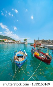 Two fishing boats moored at pier with entrance to fortified medieval harbour of Nafpaktos behind under blue sky on Peloponnese Peninsula Greece.