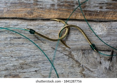 Two fishing hooks tied with fishing line on a wooden background.