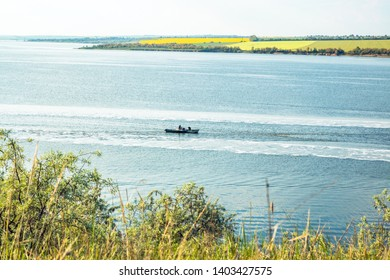 two fishing motor boats are trawl in the lake, green fields on the background