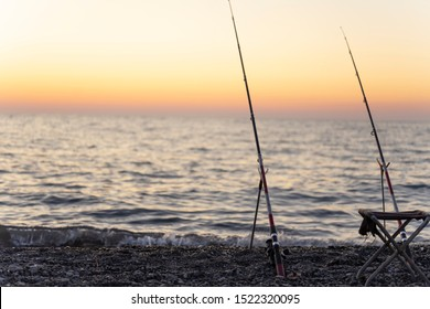 Two fishing rods held in fishing rod holders, with reel on sea sunset background. Fishing from the shore
