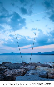 Two fishing rods standing vertically on the cliffs by the sea in sunrise light with blue cloudy sky