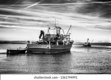 two fishing trawlers leave the port in early evening, black and white classic photo