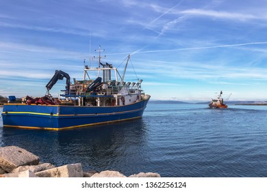 two fishing trawlers leave the port in early evening