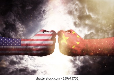 Two fists hitting each other over dark sky, Usa and China conflict