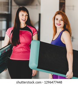 Two fit healthy women doing step aerobics in fitness club