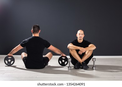 Two fit males sitting at the floor of the gym studio,looking in opposite direction,having Pilates equipment around them