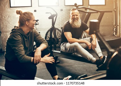 Two fit people smiling and talking together while taking a break from working out on rowing machines at the gym