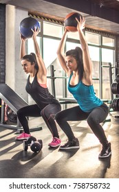 Two fit sporty girls exercising together with pilates balls in t