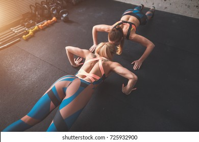 two fit woman in fitness salon in push up pose exercise