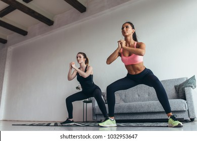 Two fit women doing squats at home Female workout sport and fitness.