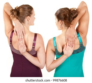 Two fit women stretching their arms over white background