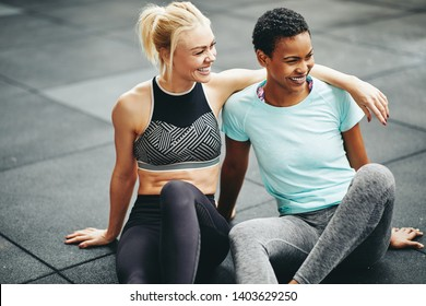 Two fit young female friends in sportswear laughing after a workout while sitting on the floor of a gym