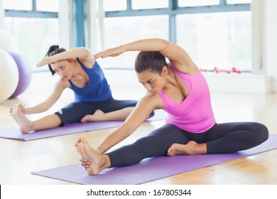 Two fit young women doing stretching pilate exercises in fitness studio