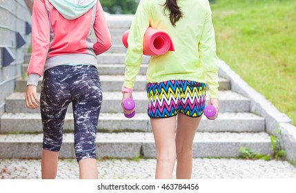 Two fit young women friends holding fitness mat and weights walking up stairs in a park, outdoor workout concept