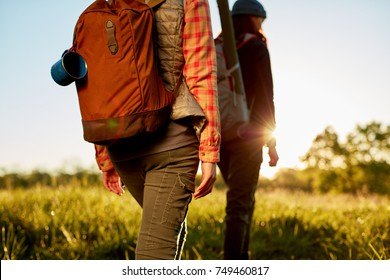 Two fit young women on an early morning hike walking through a field with their backpacks lit by a sunburst of the rising sun
