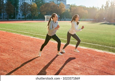 Two fitness running female jogging on athletics stadium track, open air during hot summer morning.
