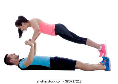 Two fitness trainers doing a face to face push-up while smiling. Image isolated on white background.