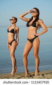 Two fitness women clad in black bikinis posing on the beach