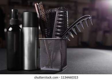 two flacons of professional hair sprays near a basket with hairbrushes standing on a table in a salon. concept of hair caring tools. free space for advertising