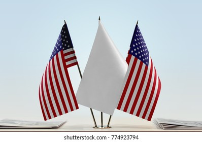 Two flags of United States of America with a white flag in the middle