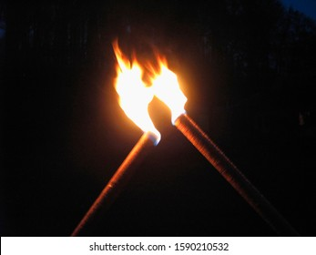 Two flaming torches in dark