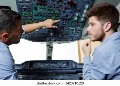 two flight engineers talking in cockpit