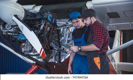 Two flight mechanics doing a pre flight check or maintenance on a small single engine aircraft in a hangar in a close up view of them working on the engine.
