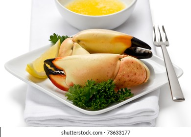 Two florida stone crab claws on appetizer plate with slice of lemon, and a side of melted butter.