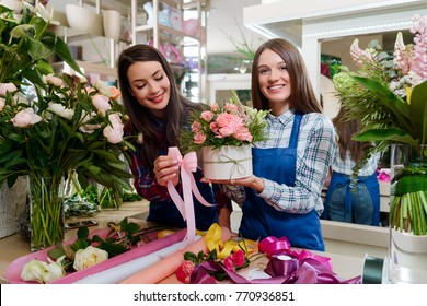 Two florists creating a gift for a birthday. Gorgeous combination of roses, lupines and grass in the box, being decorated with a bowknot.