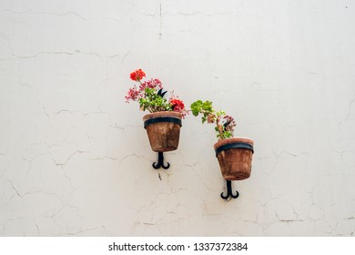 two flower pots hanged on white building wall