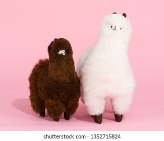 Two fluffy alpaca toys made of genuine alpaca hides on pink background
