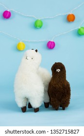 Two fluffy alpaca toys made of genuine alpaca hides on festive blue background