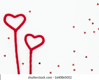 Two fluffy red hearts made from pipe cleaners with scattered heart glitter on white background