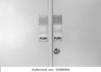 two flush doors with metallic push sign and door knob in black and white style.