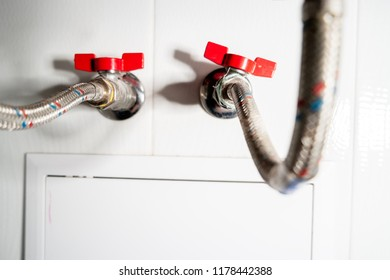 Two flwxible pipes with red valves shot with copyspace and dutch angle