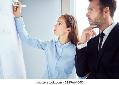 Two focused coworkers looking at flipchart with company performance statistics