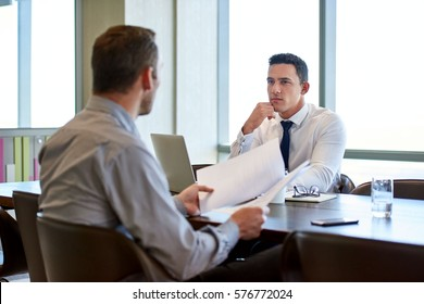 Two focused coworkers sitting together at a desk in a modern office deep in discussion over documents