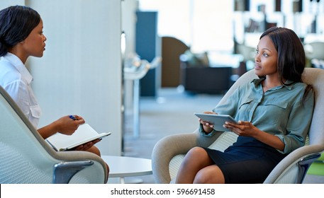 Two focused young business colleagues sitting in chairs talking together while having a meeting in a modern office