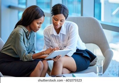 Two focused young business colleagues talking over a digital tablet while having a meeting together in a modern office