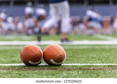 Two football balls lined up on the field line