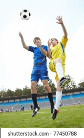 Two footballers jumping and looking at ball on grass-field during game