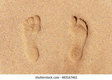 Two footprint on sandy beach