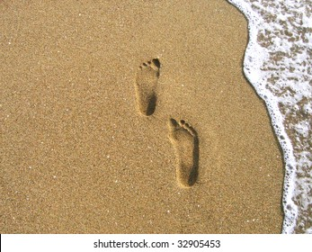 Two footprints on a sand, sea foam on the right side. Photo made on the Puerto Rico beach.