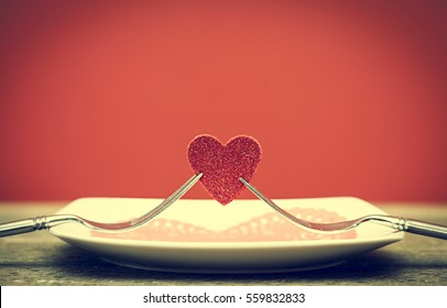 two forks holding red heart on wooden board, Valentines Day dinner