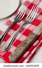 Two forks and a knife on a red and white checkered napkin. Informal table setting.