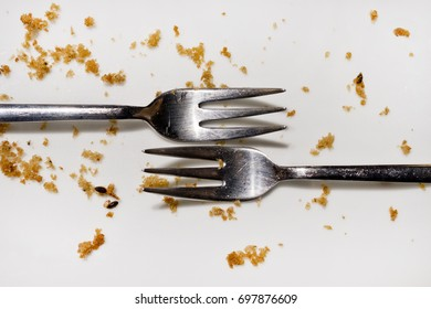 Two forks on an empty dish.